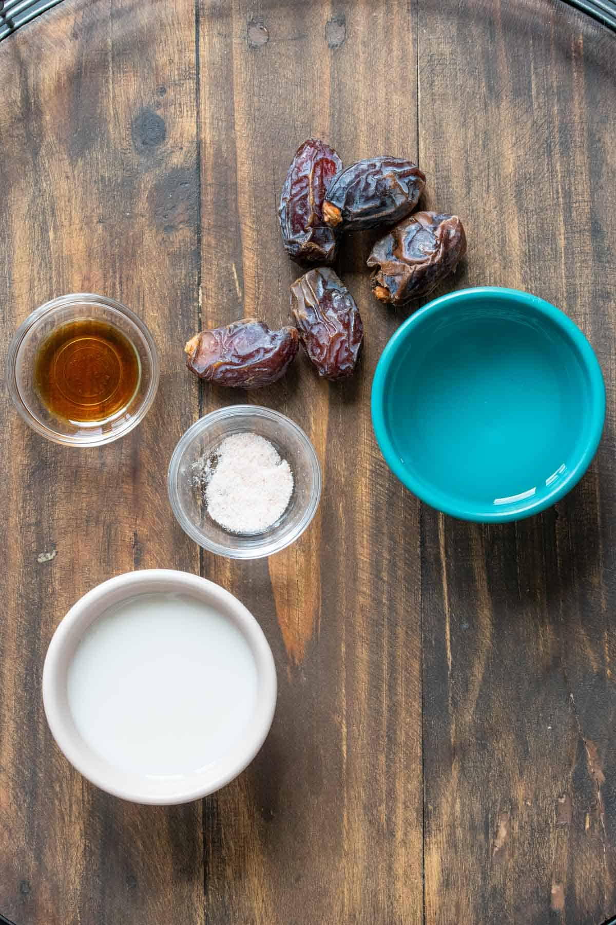 Dates, water, milk, salt and vanilla on a wooden table