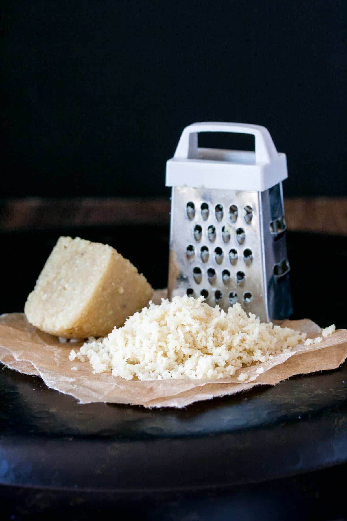 A pile of grated Parmesan next to a grater and a piece of the cheese block