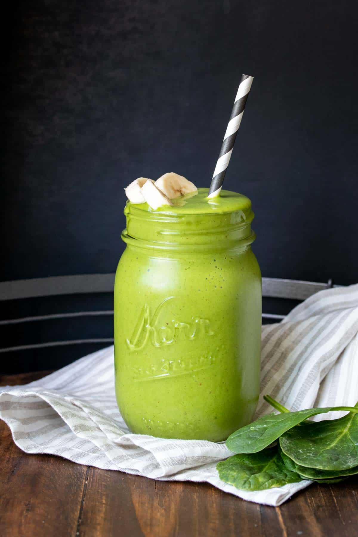 A green smoothie with sliced bananas on the top in a glass jar