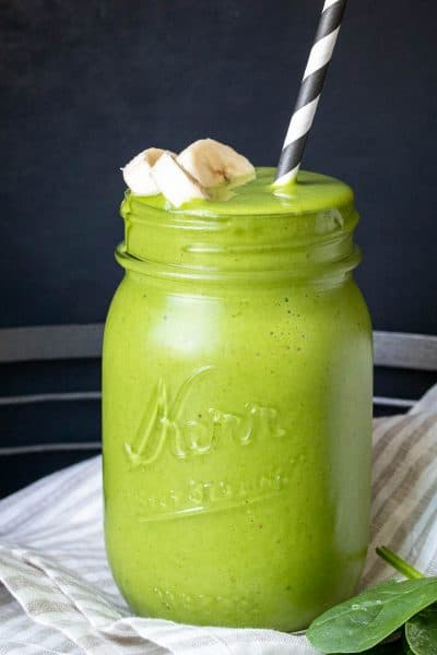 A glass jar with a green smoothie and straw in it