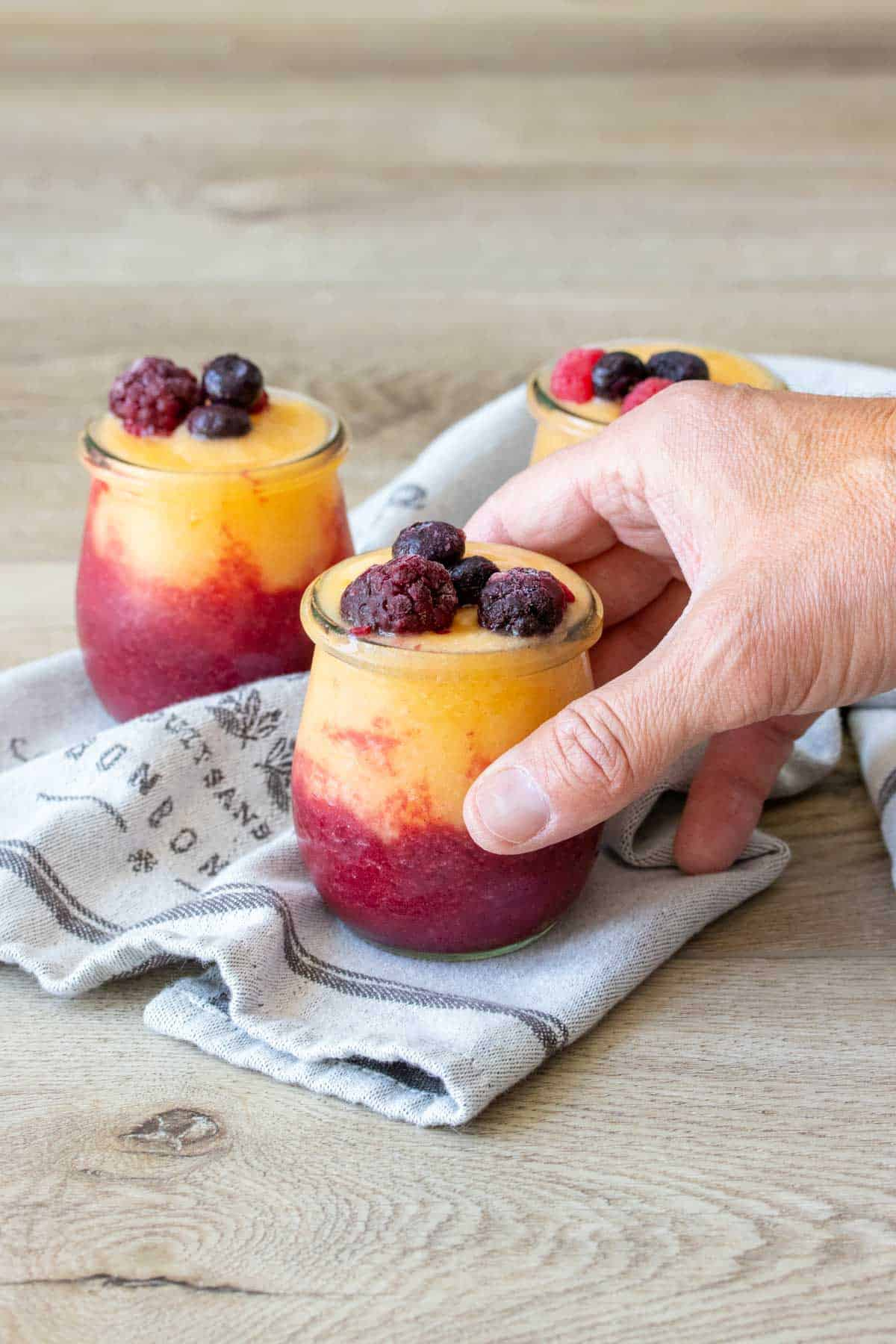 Hand grabbing a jar filled with a wine slushie topped with fruit