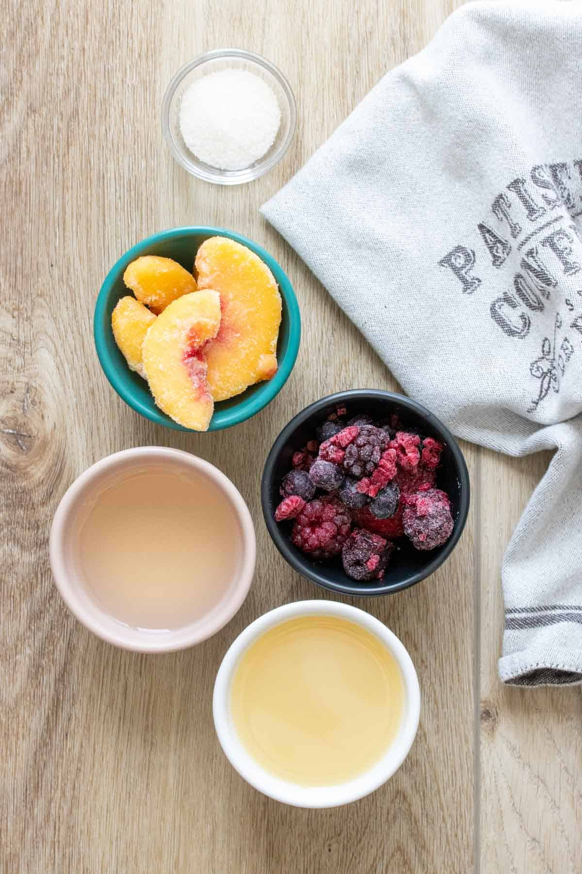 Bowls with frozen fruit, wine and lemon juice on a wooden surface