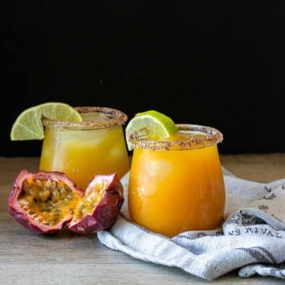 Two glasses with orange drinks in them and limes on the rim