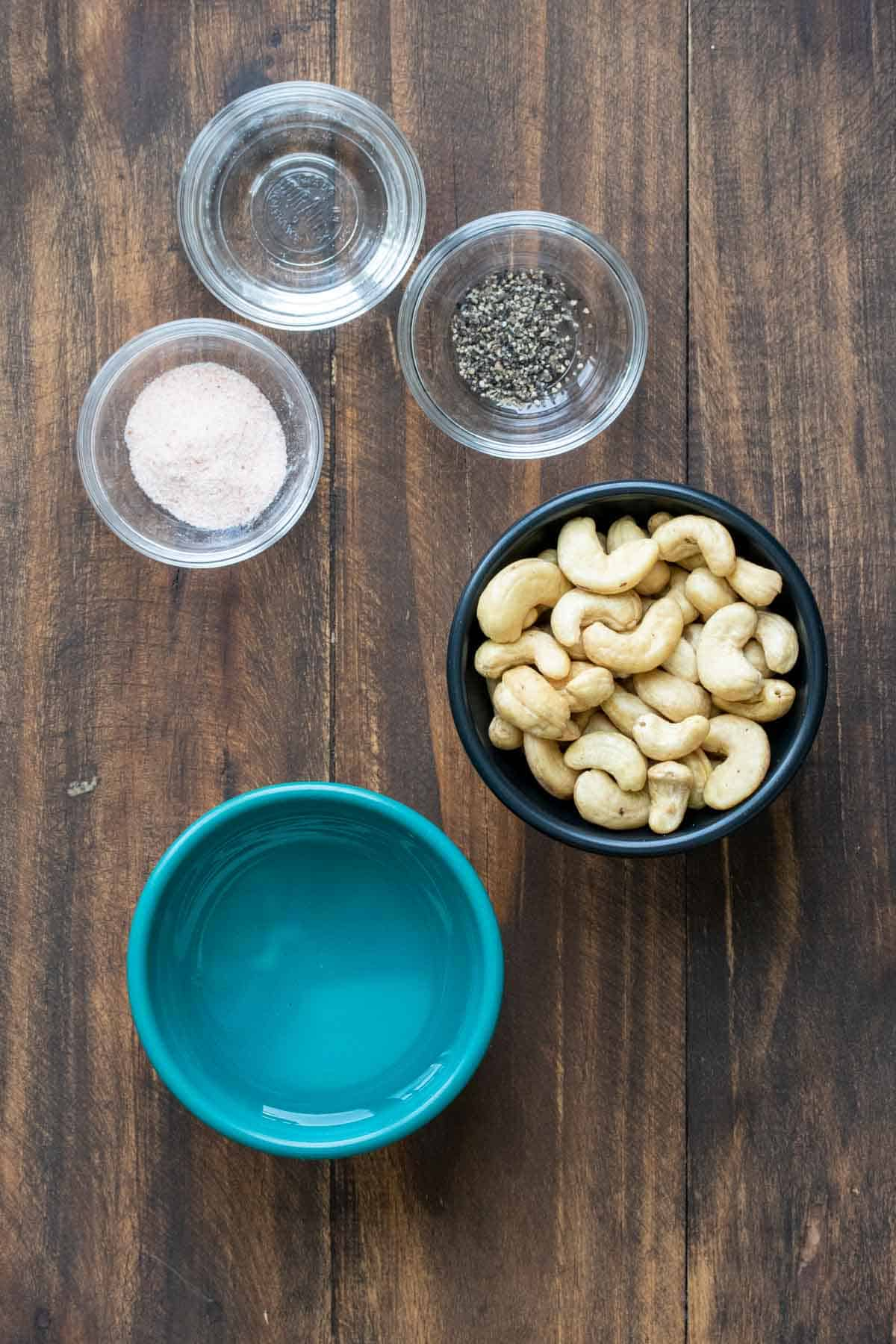 Bowls with cashews, water, salt, pepper and vinegar on a wooden surface