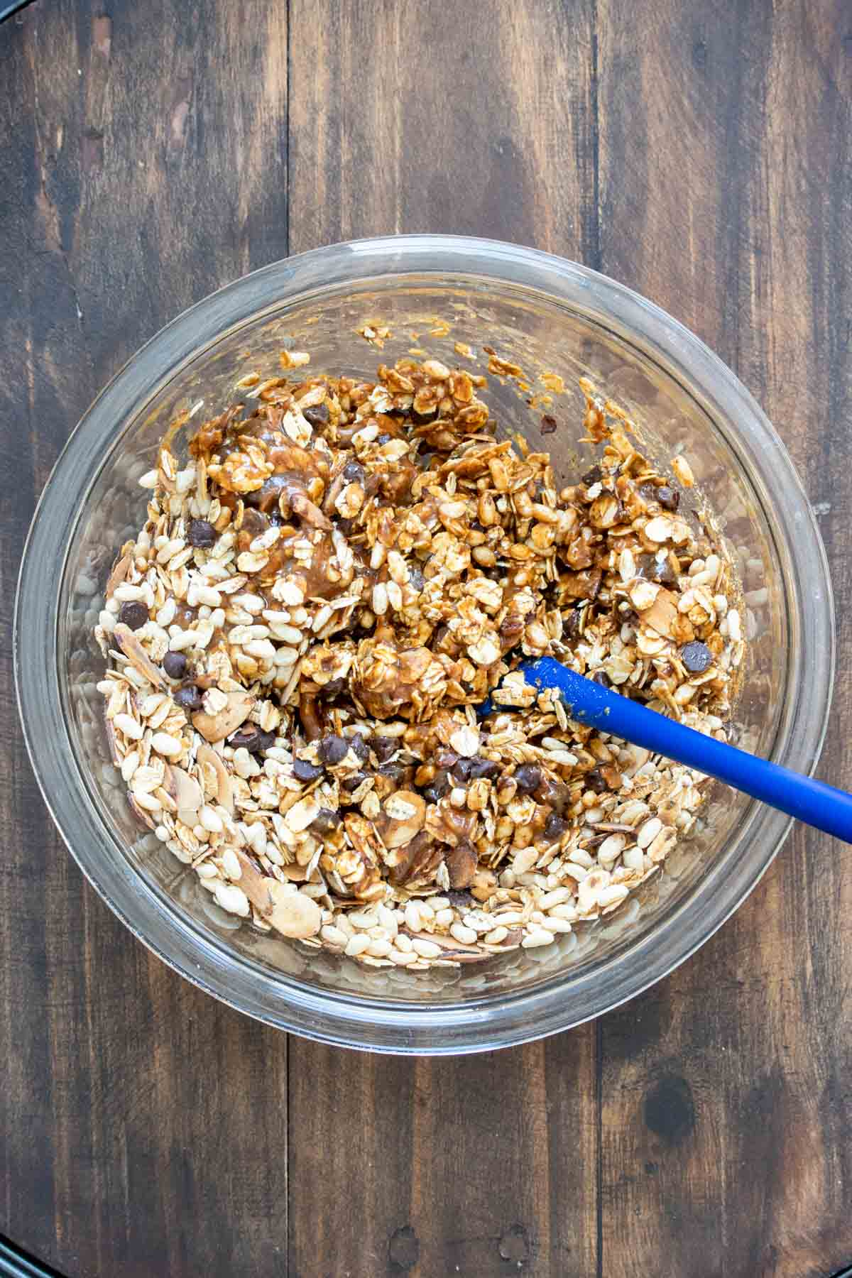 Spatula mixing oats and a brown sticky mixture in a bowl
