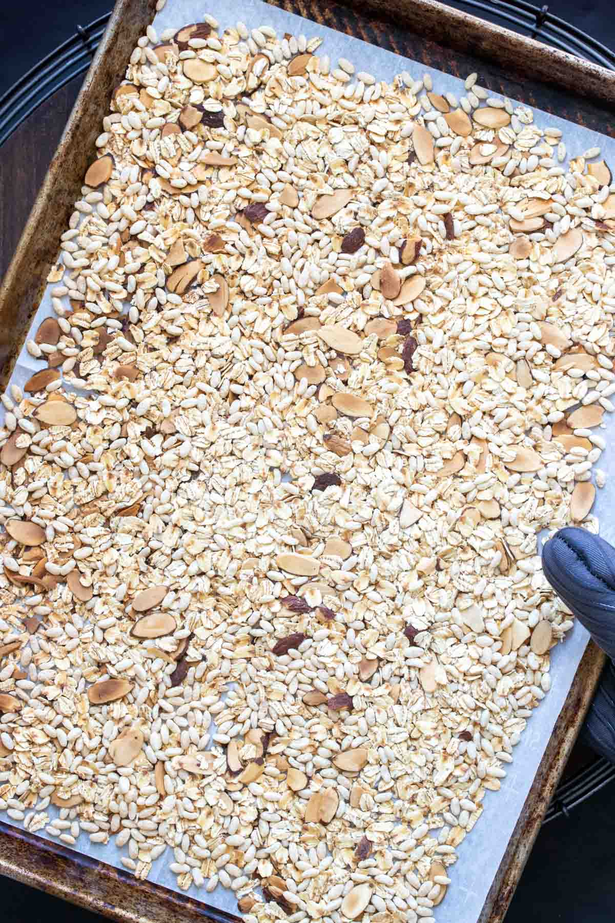 Baking sheet with oats, rice cereal and sliced almonds on it