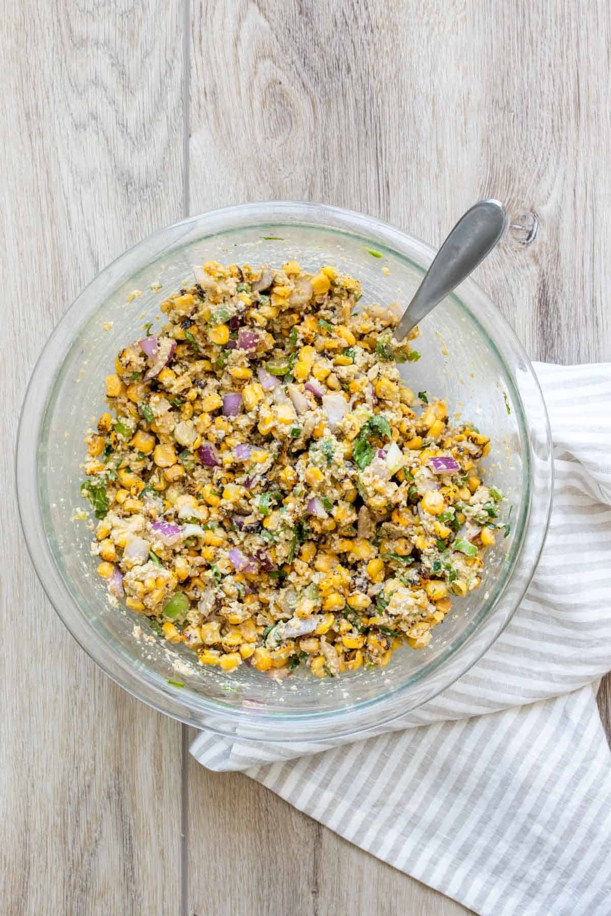 A glass bowl with mixed up corn salad inside