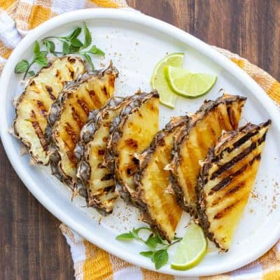 Slices of pineapple with grill marks on a white platter sitting on a yellow checked napkin