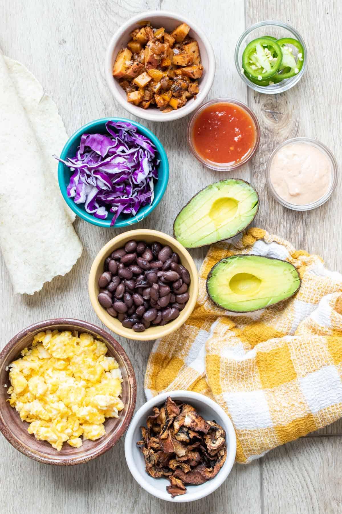 Bowls with ingredients to make breakfast burritos on a wooden surface and yellow checkered towel