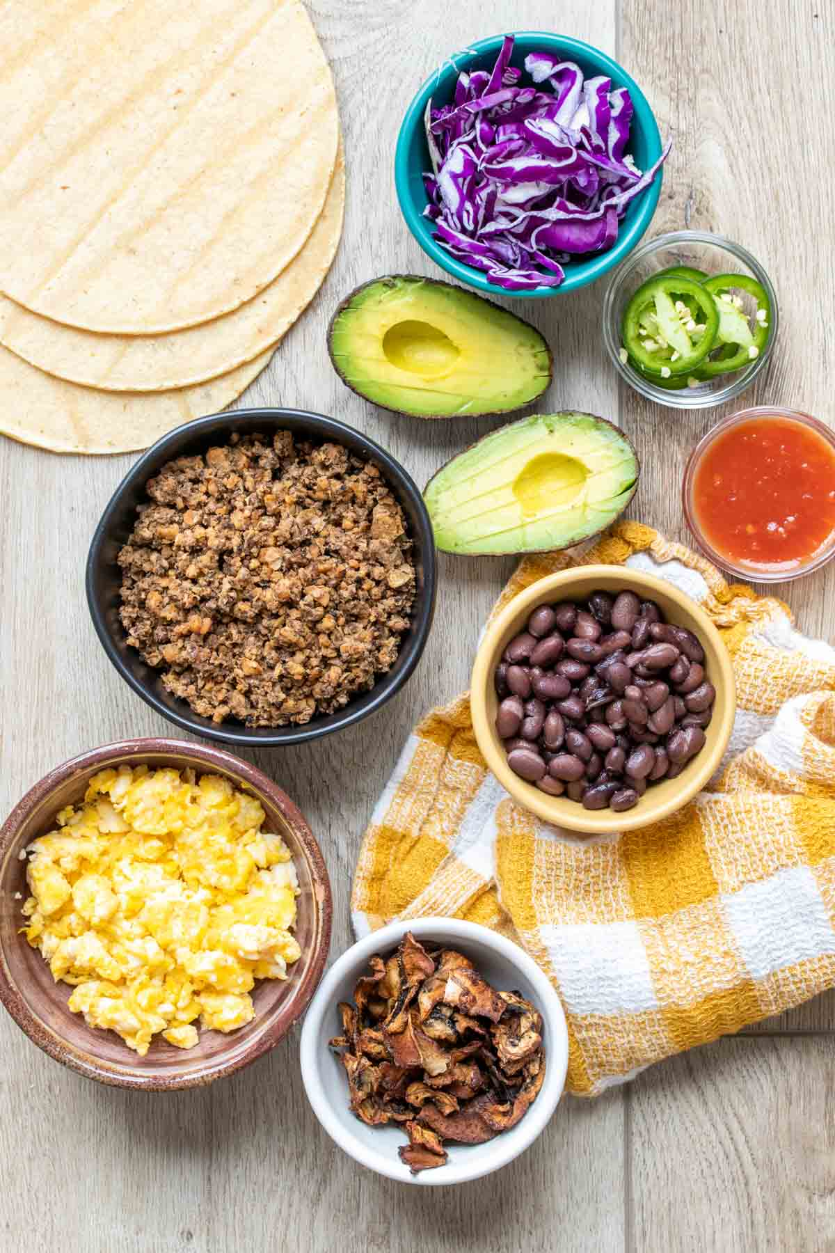 Ingredients in bowls needed to make breakfast tacos next to tortillas and avocado halves