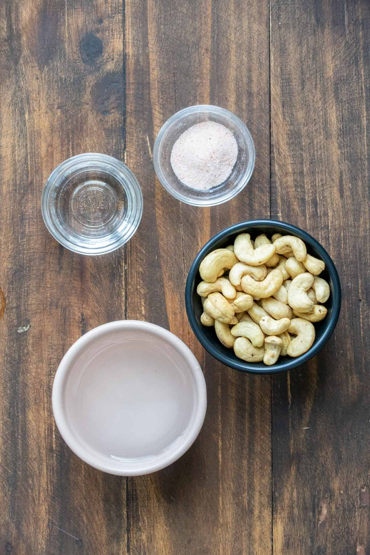 Bowls of cashews, water, salt and vinegar on a wooden surface