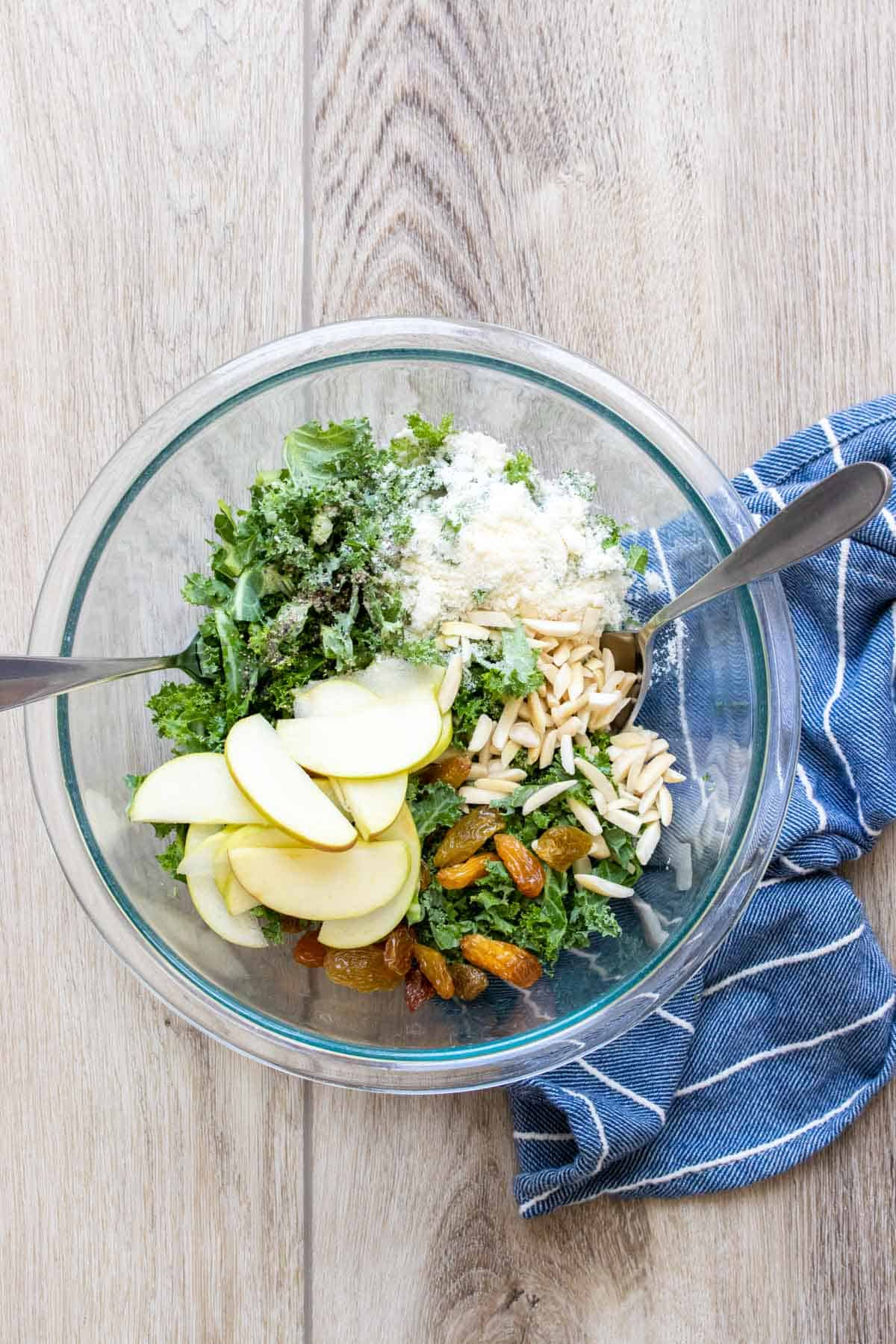 A glass bowl with kale, apples, nuts and Parmesan before being mixed