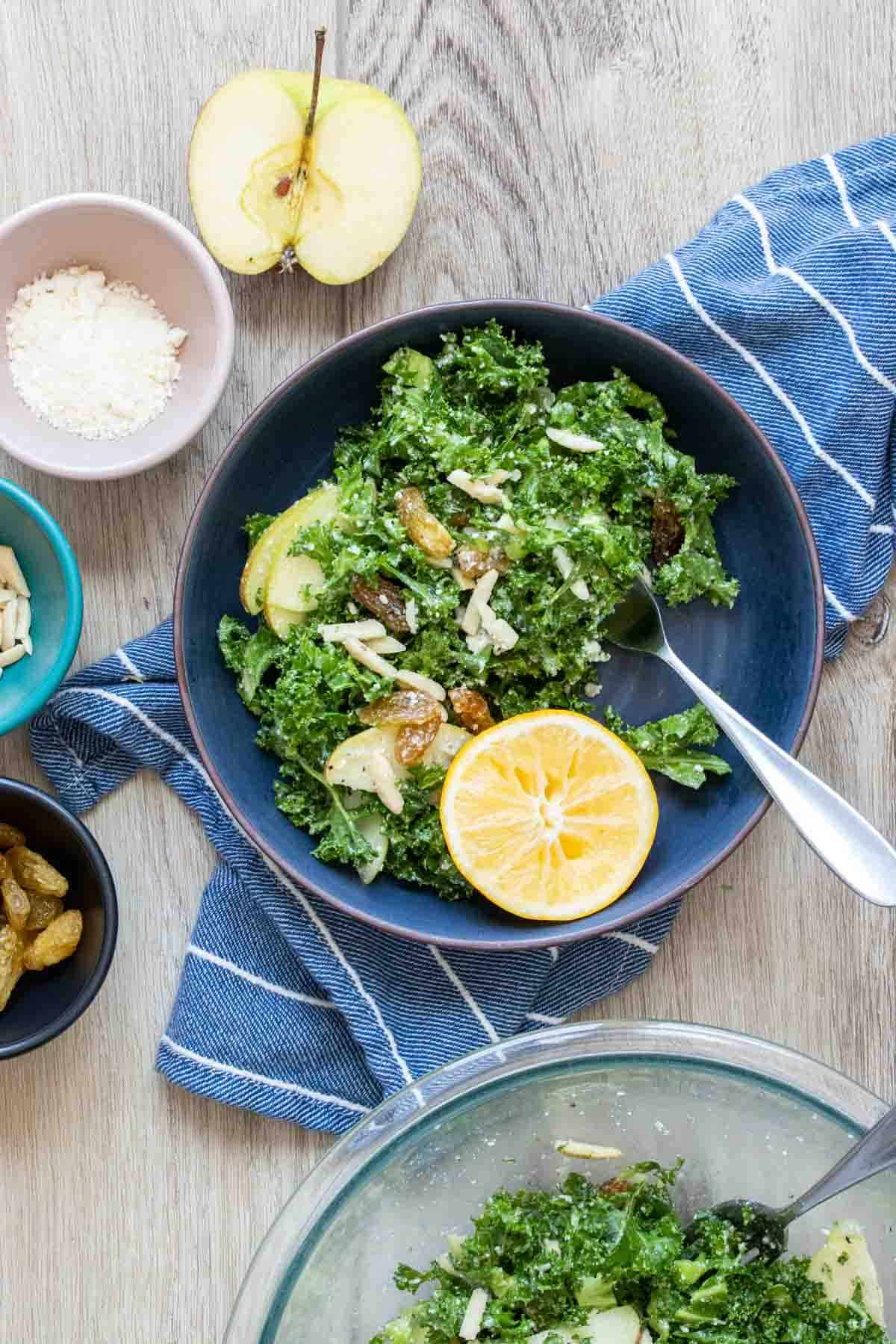 Blue bowl filled with kale salad surrounded by bowls of toppings