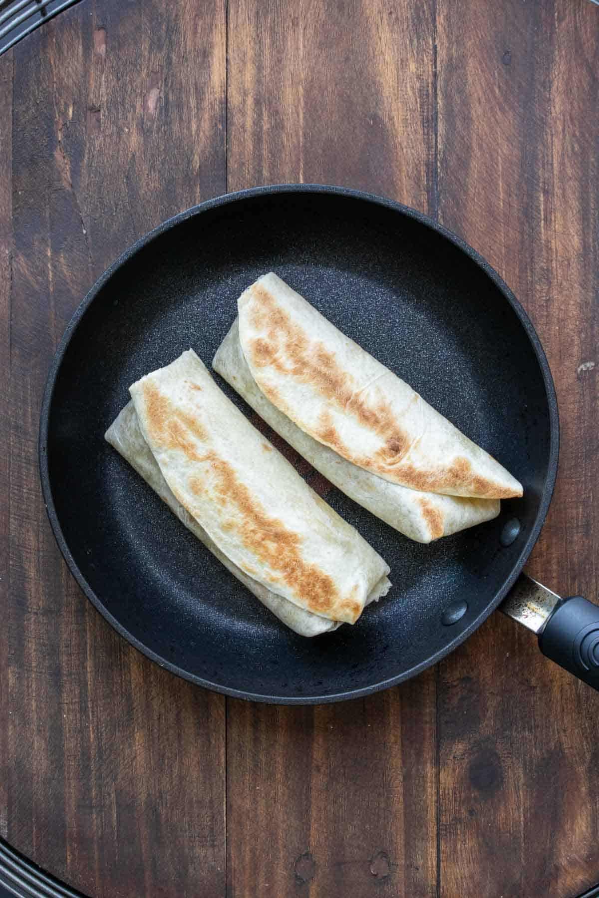 Pan with two burritos grilling on it