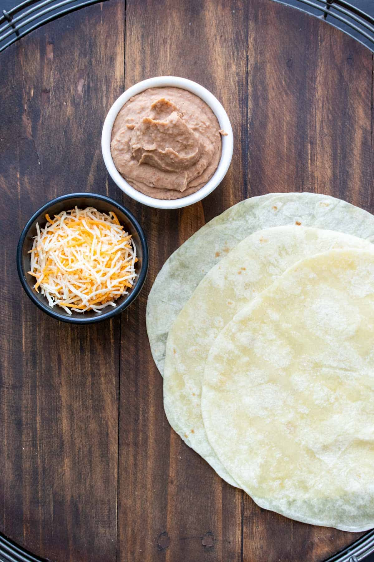 Photo of tortillas and bowls of refried beans and shredded cheese on a wooden surface