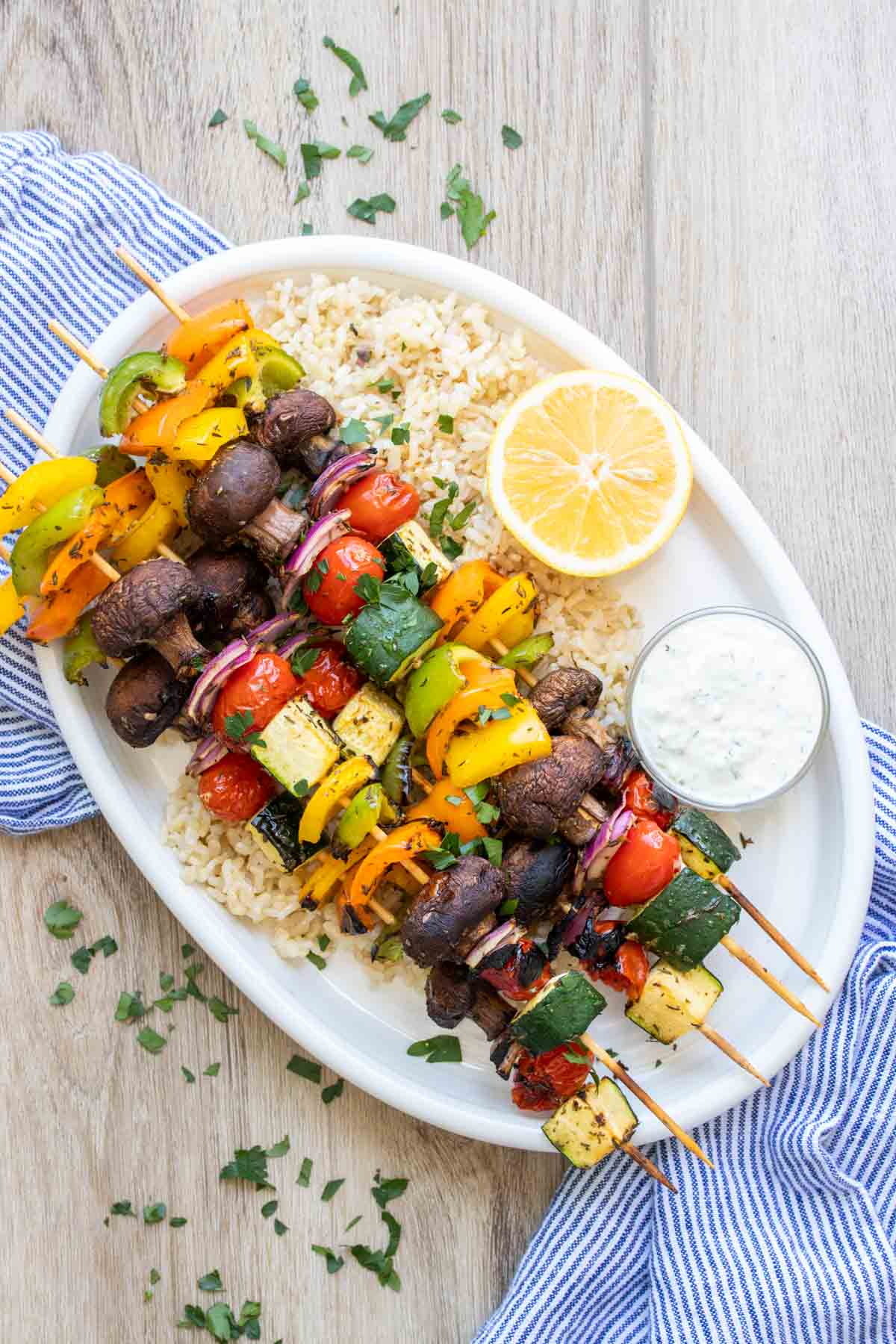 White platter on a blue towel with rice and veggie kabobs on it
