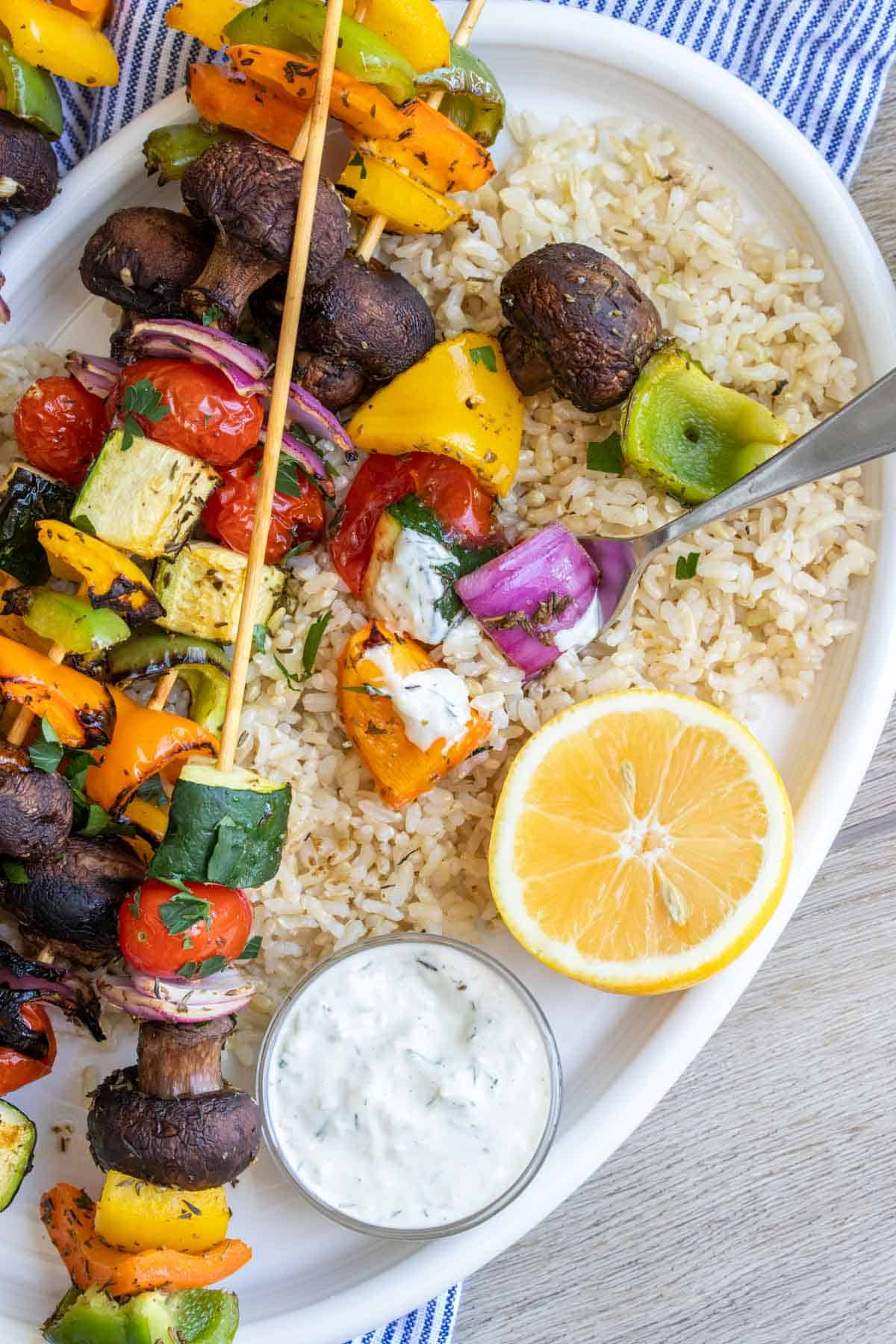 A half eaten veggie kabob on top of full kabobs sitting on a bed of rice on a plate