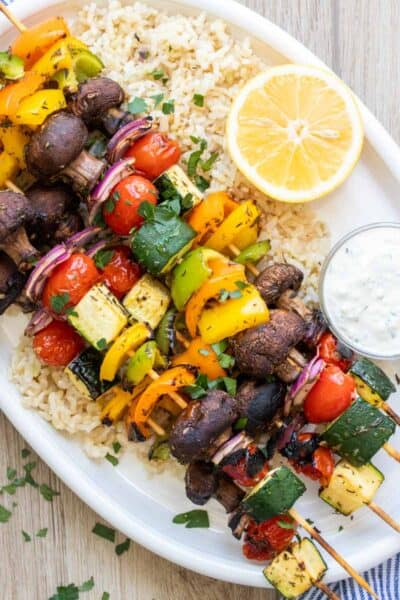 White platter with veggie kabobs, rice and white sauce on it