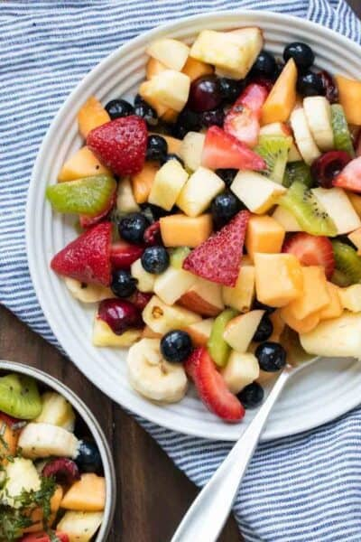 Fruit salad in a bowl on a blue striped towel and a turquoise border around