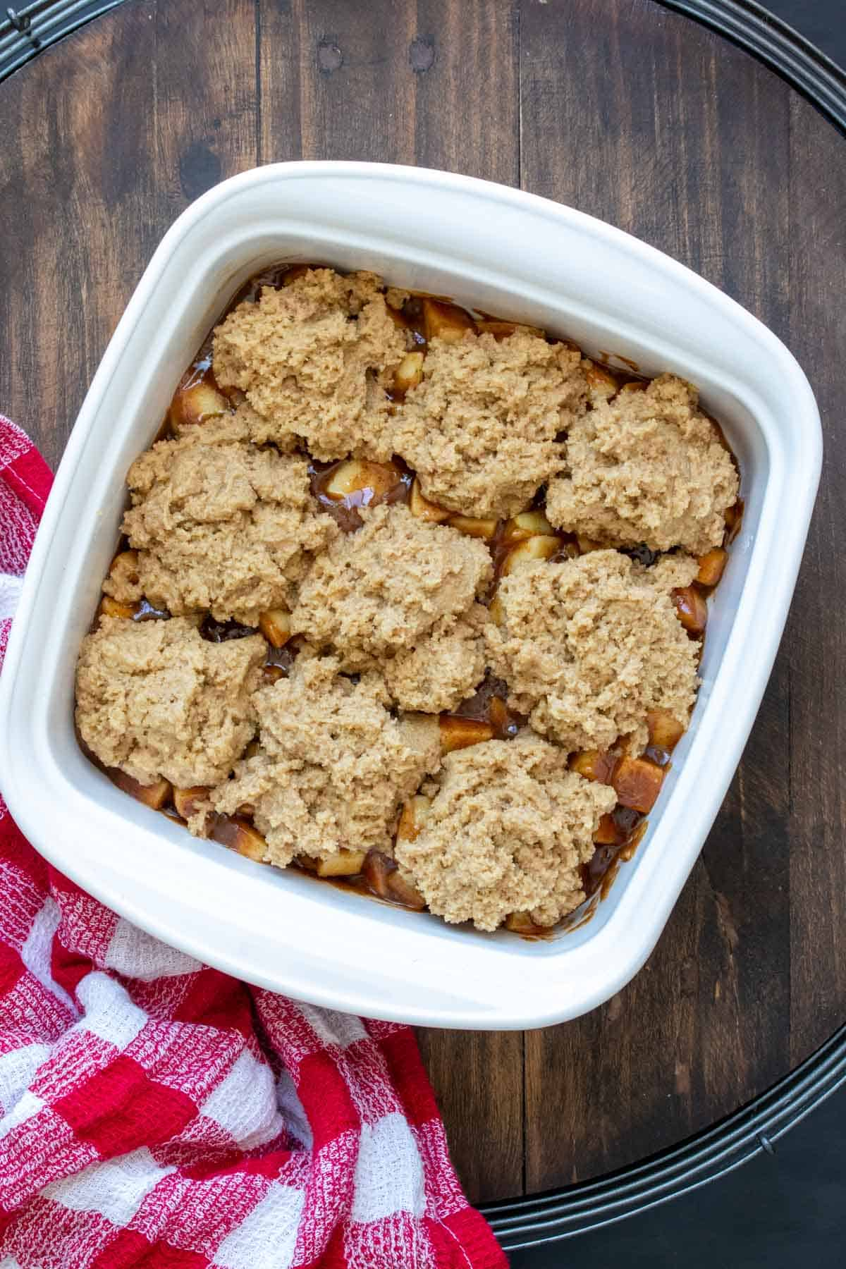 Square white baking dish with raw apple cobbler inside