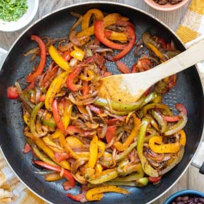 Wooden spoon mixing cooking peppers and onions in a pan