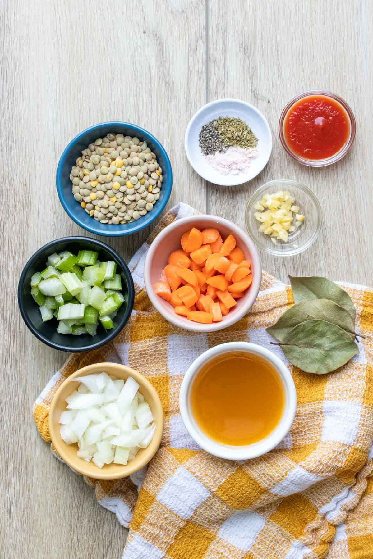 The ingredients needed for a veggie lentil soup in bowls on a yellow and white towel