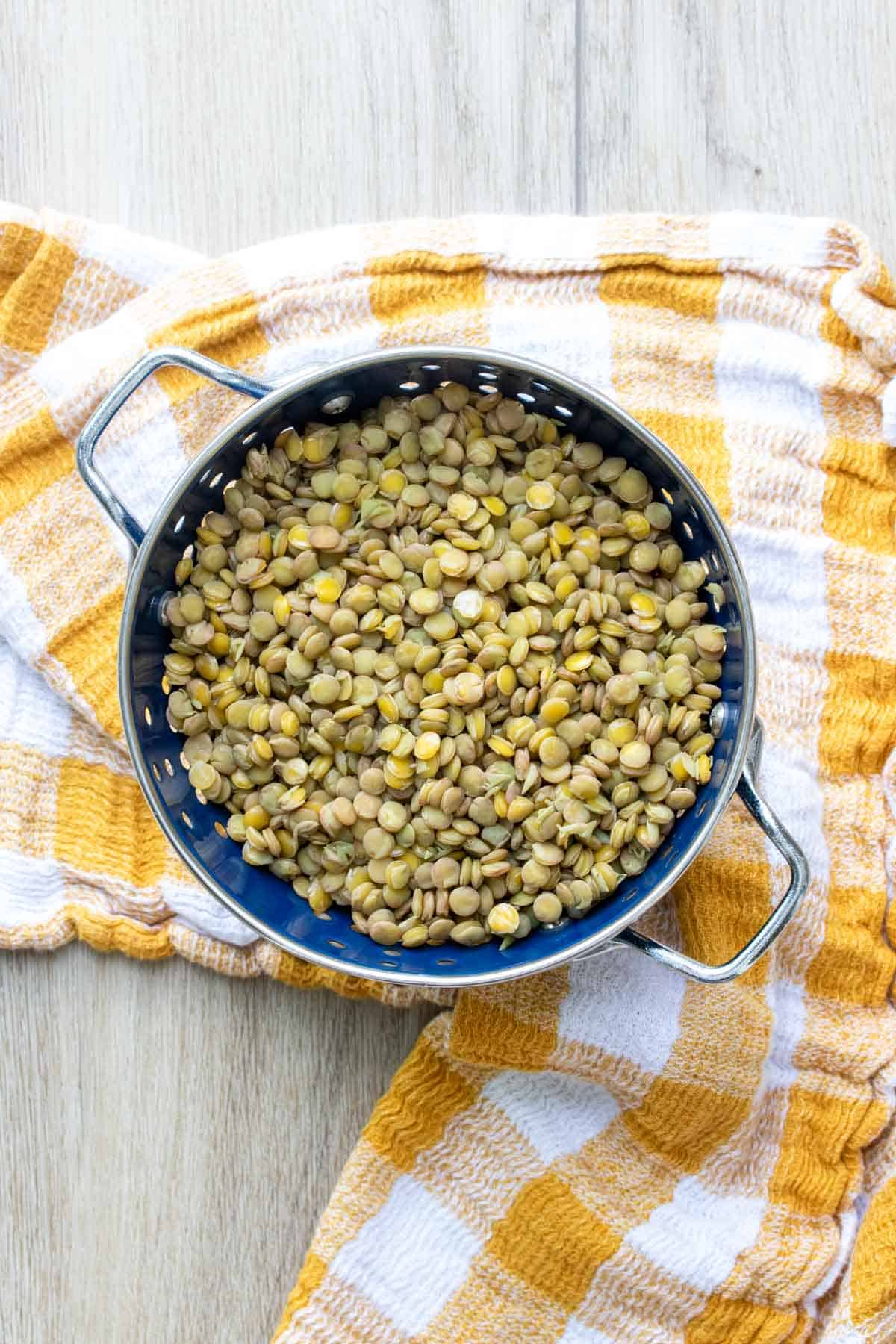 A blue colander filled with lentils on a yellow checkered towel