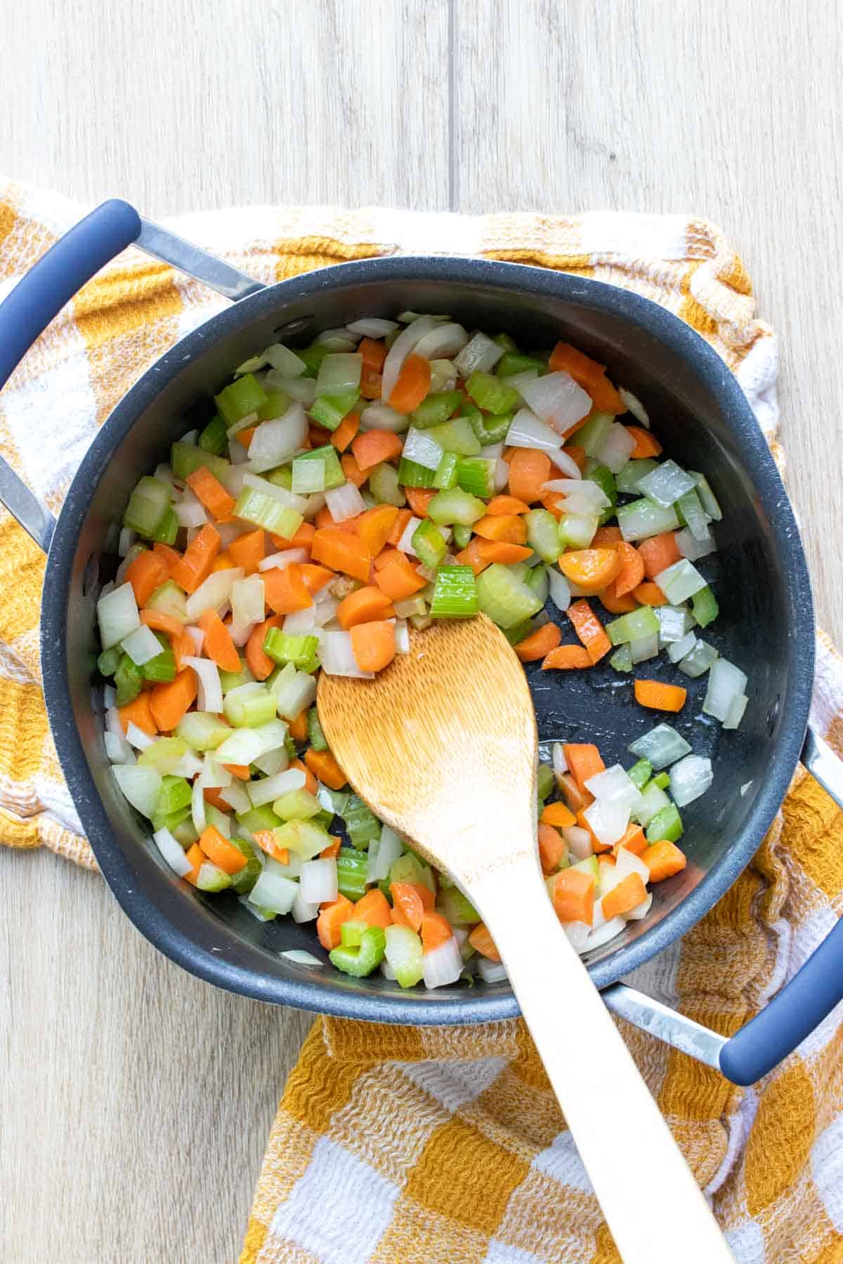 Wooden spoon mixing carrots, celery and onion in a pot on a checkered towel