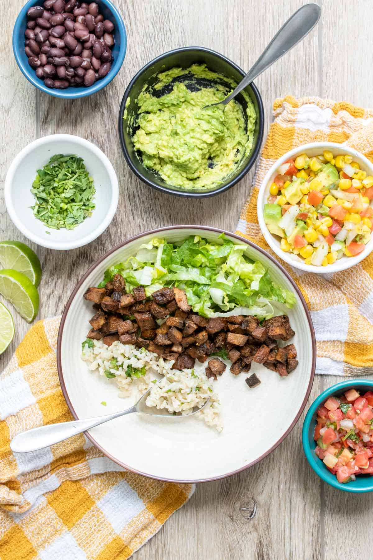 White bowl with piles of lettuce, beans and rice in a row inside
