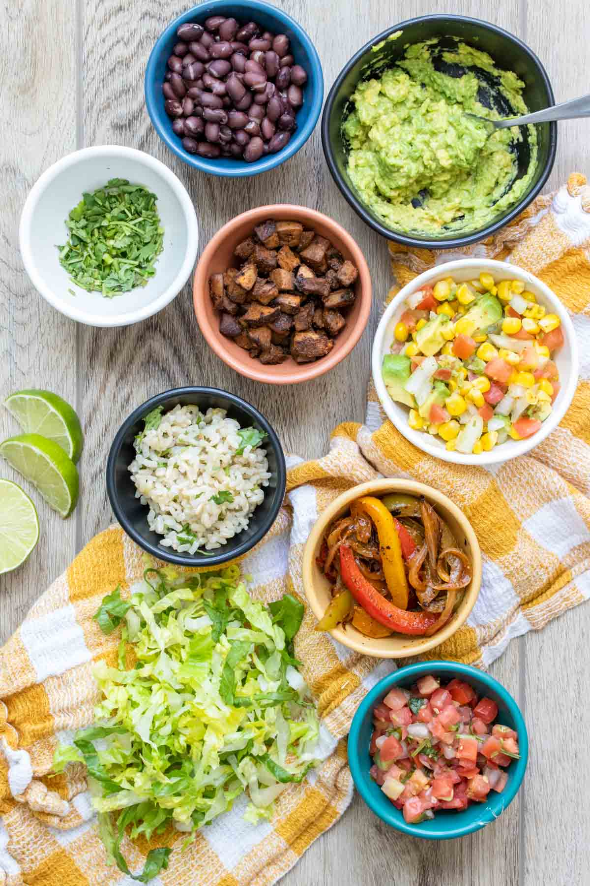 Different colored bowls on a checkered towel filled with ingredients to build a burrito bowl