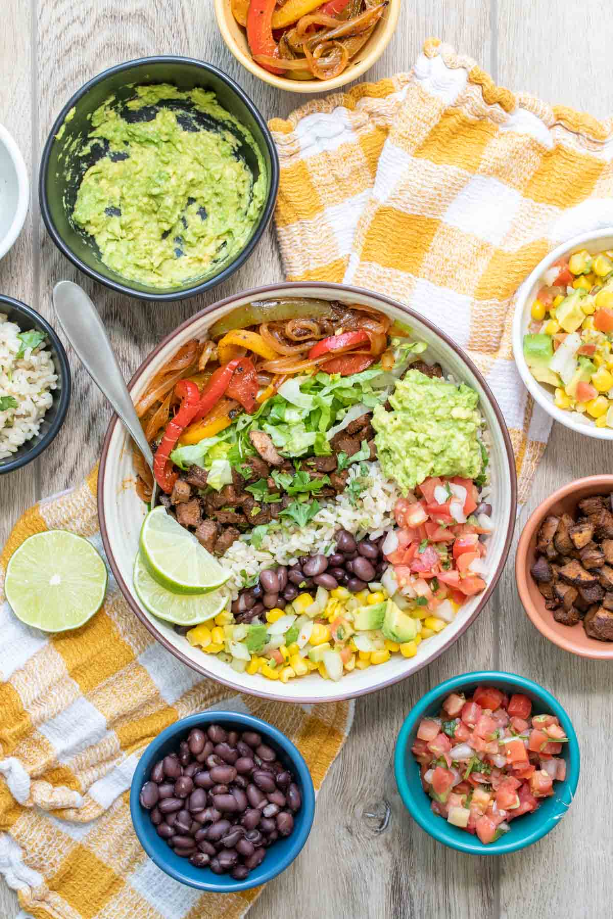 Bowl with piles of ingredients liked up to make a burrito bowl surrounded by small bowls of ingredients