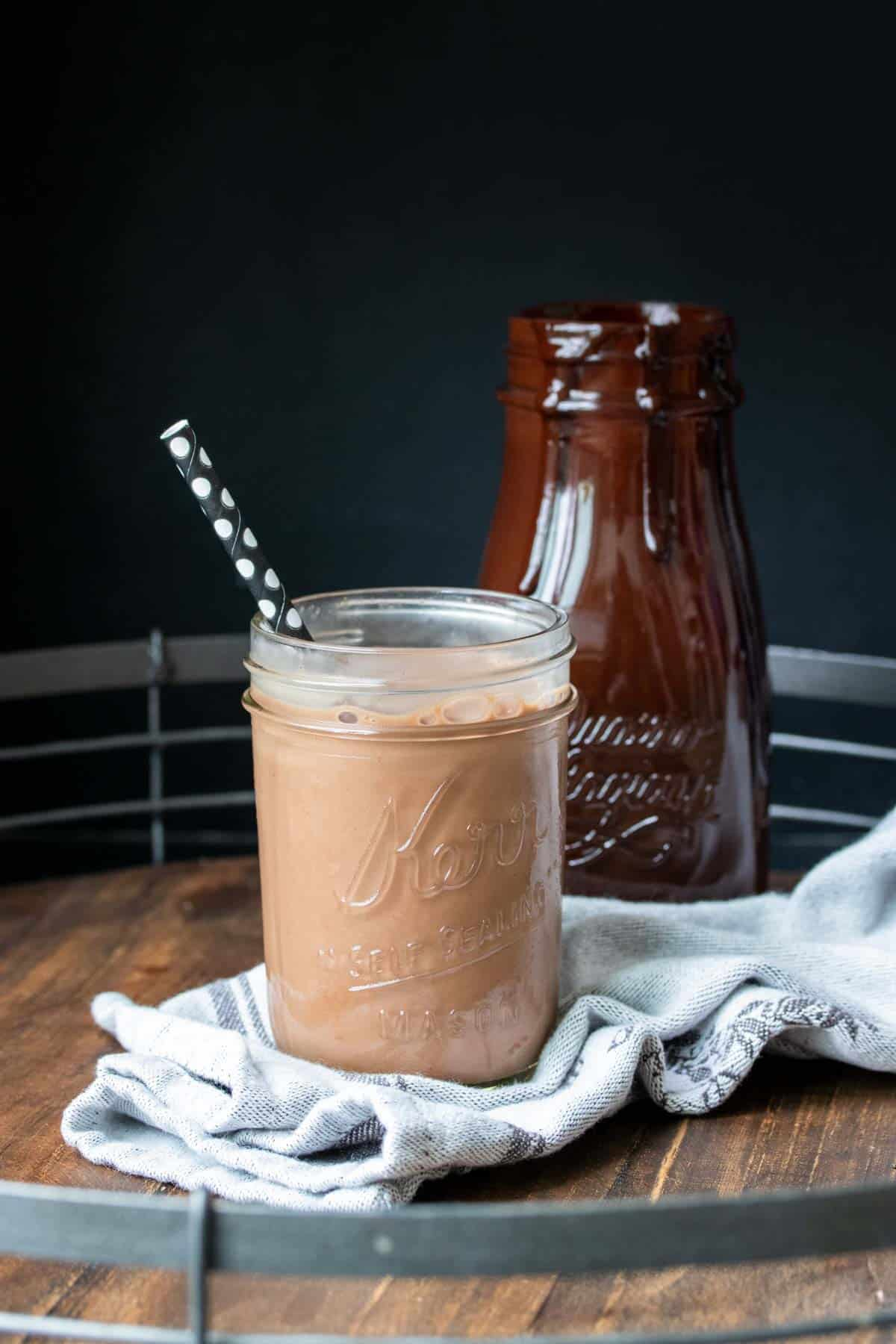 A glass jar filled with chocolate milk and a black straw