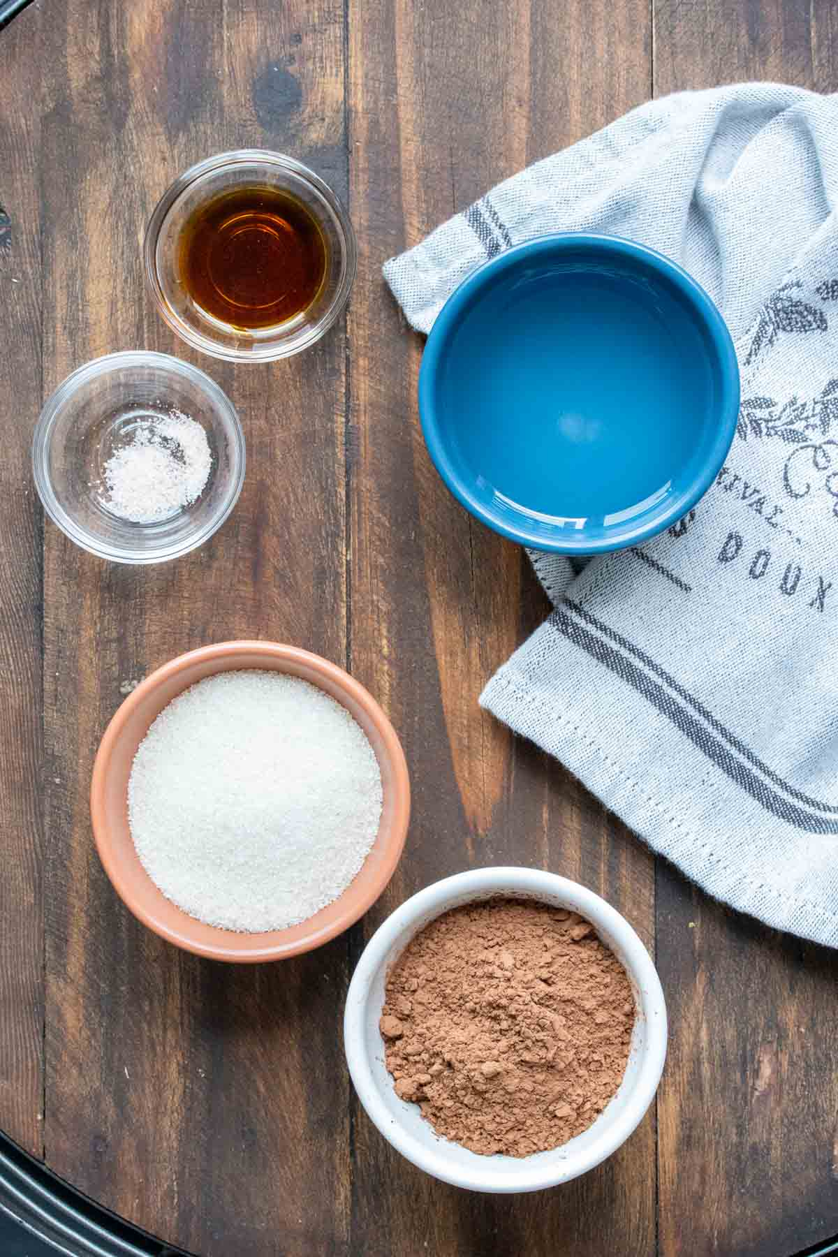 Ingredients needed to make homemade chocolate syrup in bowls in a wooden surface