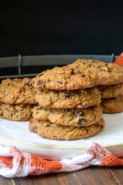 Cream colored plate sitting on an orange checkered towel piled with chocolate chip cookies