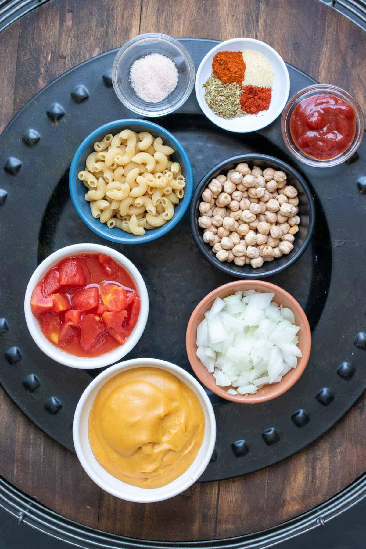 Black platter with ingredients needed to make a vegan hamburger helper macaroni dish