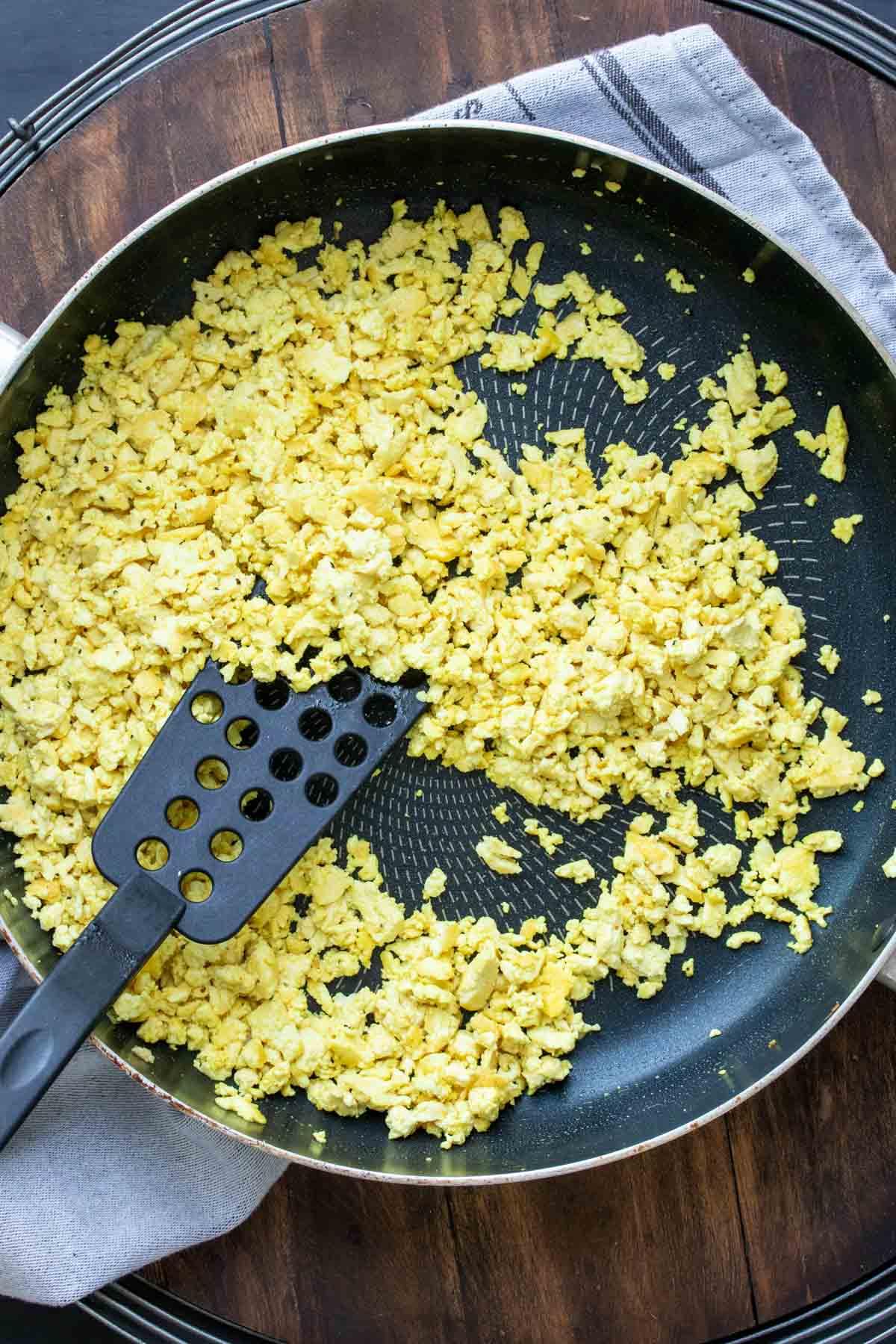 Spatula cooking yellow crumbled tofu in a pan