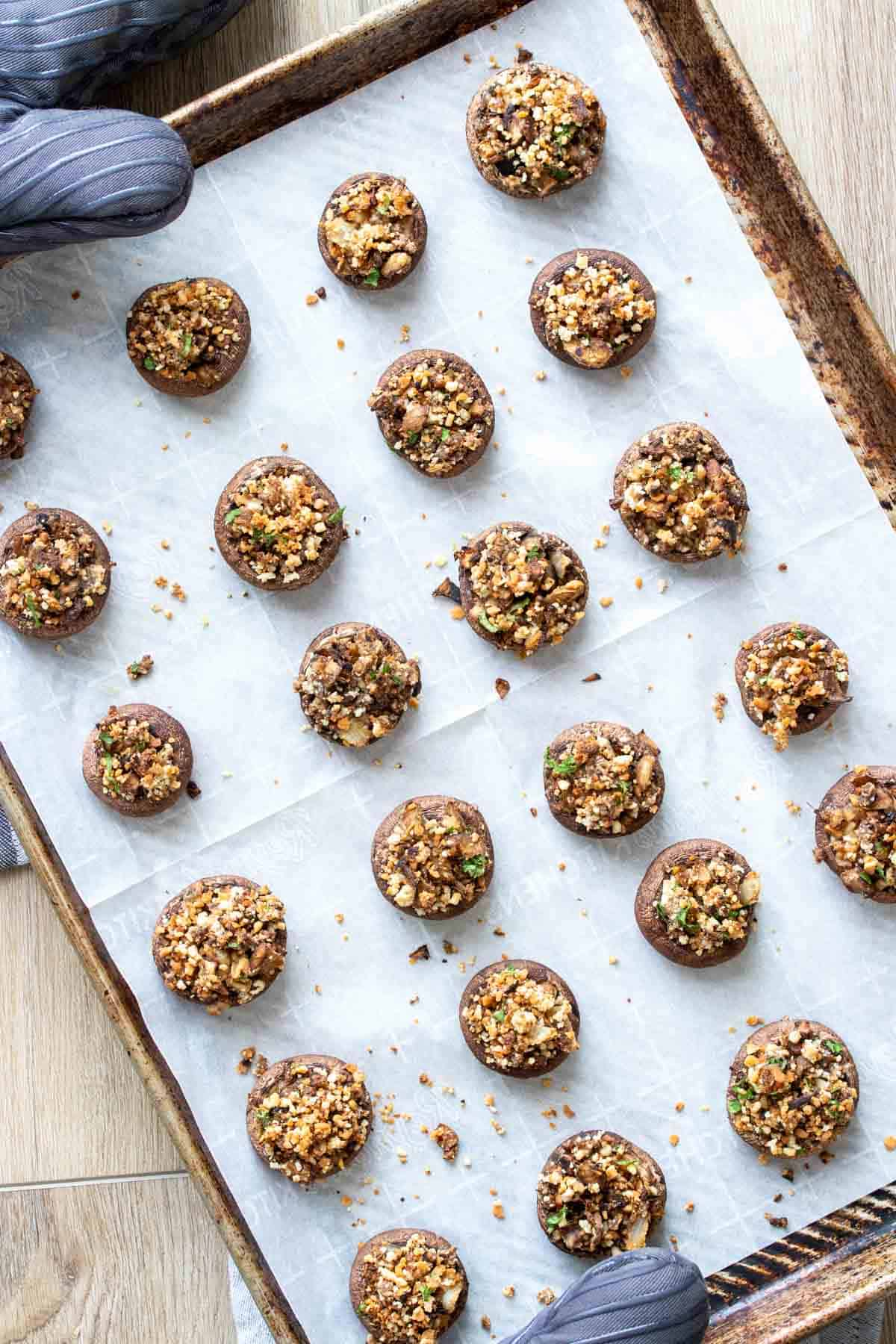 Top view of a parchment lined baking sheet filled with baked stuffed appetizer mushrooms